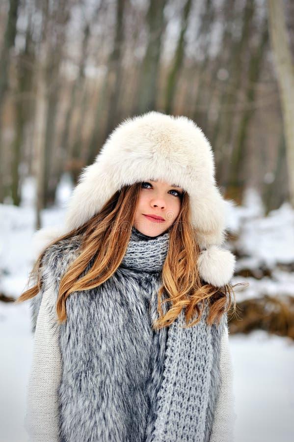 Menina bonita com cabelo encaracolado longo no lenço feito malha e no chapéu forrado a pele que têm o divertimento exterior na fl fotografia de stock