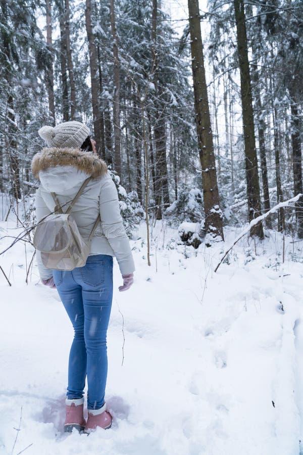 Menina bonita com cabelo escuro longo em um revestimento branco que anda em uma floresta do inverno durante uma queda de neve imagens de stock
