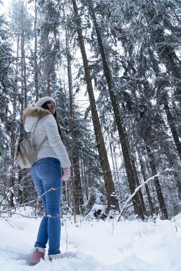 Menina bonita com cabelo escuro longo em um revestimento branco que anda em uma floresta do inverno durante uma queda de neve imagem de stock royalty free