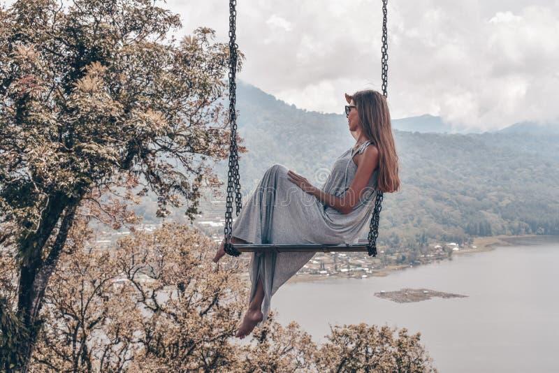 Menina bonita com cabelo escuro longo no levantamento cinzento elegante do vestido imagem de stock