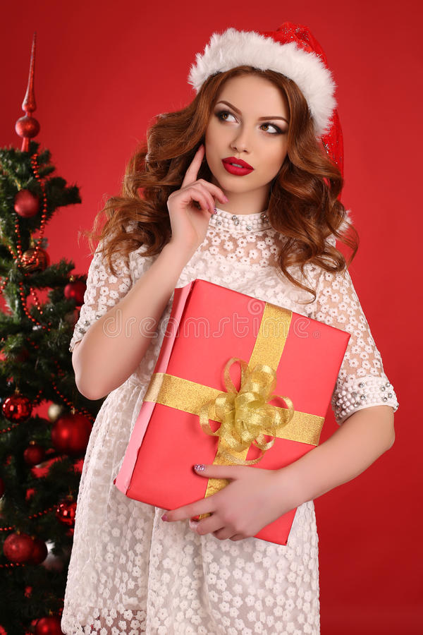 Menina bonita com cabelo escuro no vestido elegante com presente de Natal grande foto de stock royalty free