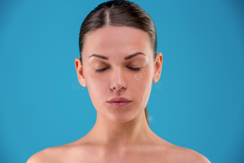Menina bonita com cabelo escuro, com os ombros despidos com olhos fechados, um modelo com composição nude clara, estúdio azul imagens de stock