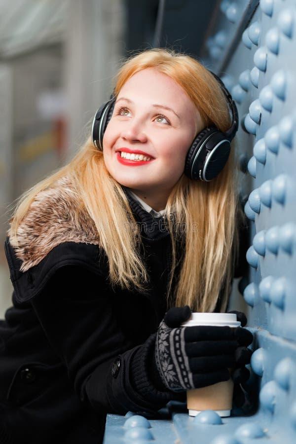 Menina bonita com cabelo longo e os fones de ouvido que estão a parede próxima imagem de stock royalty free