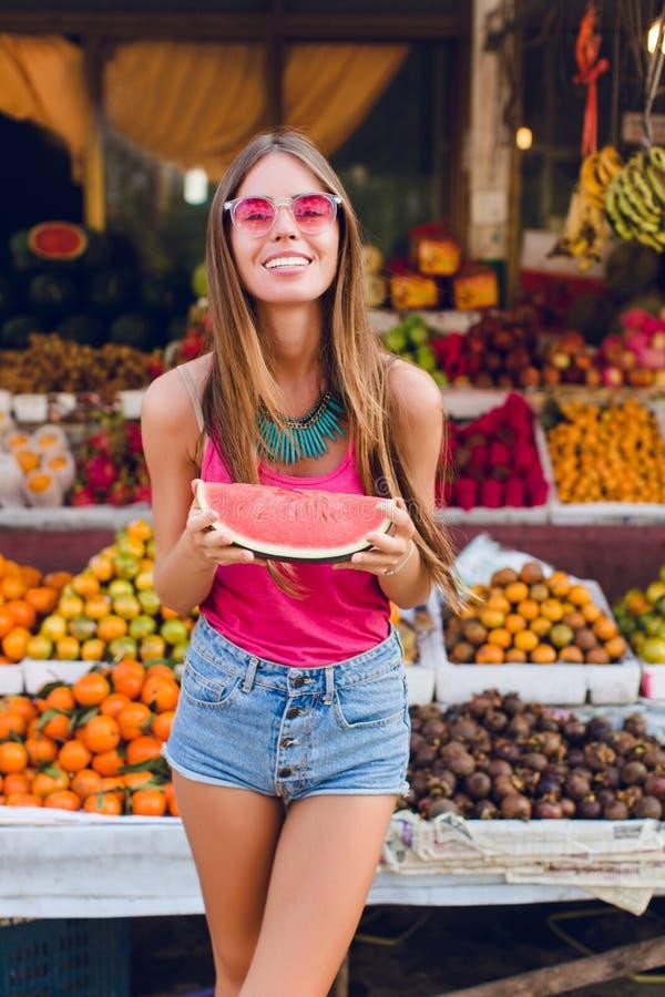 A menina bonita com cabelo longo em óculos de sol cor-de-rosa está levantando no mercado com fundo dos frutos tropicais Guarda a  fotografia de stock royalty free