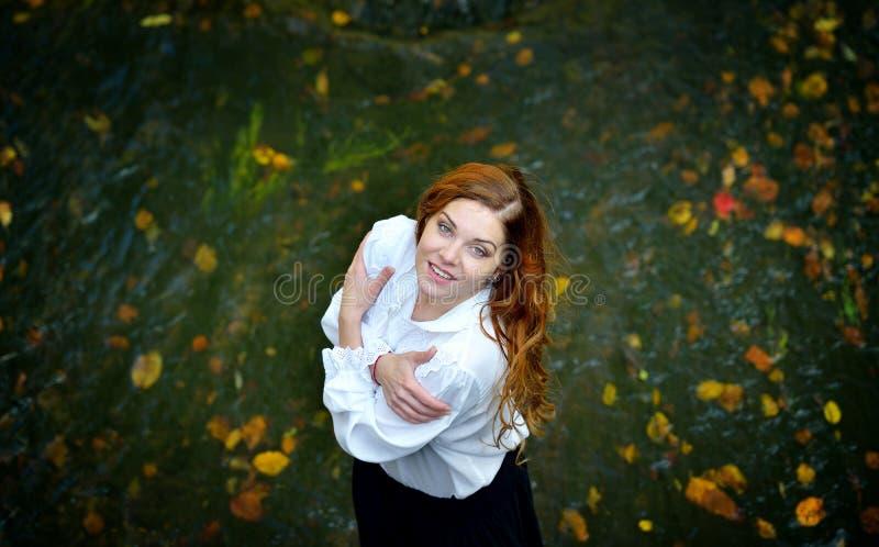 Menina bonita com cabelo longo na camisa branca e na saia preta que estão no rio com folhas de outono e que olham acima fotografia de stock