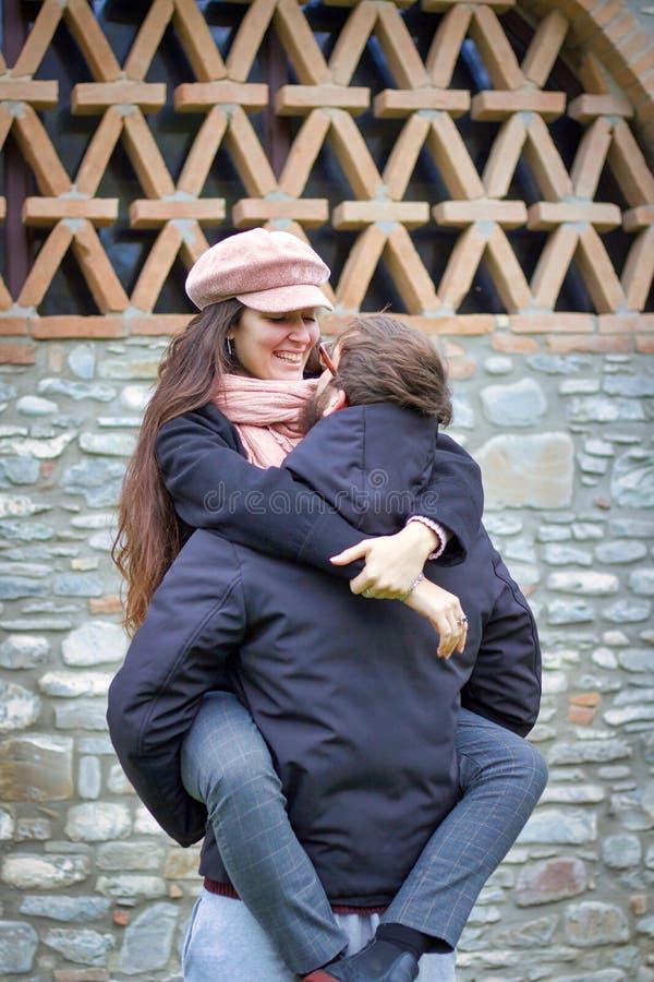 Menina bonita com cabelo longo que sorri nos braços de seu noivo fotografia de stock royalty free