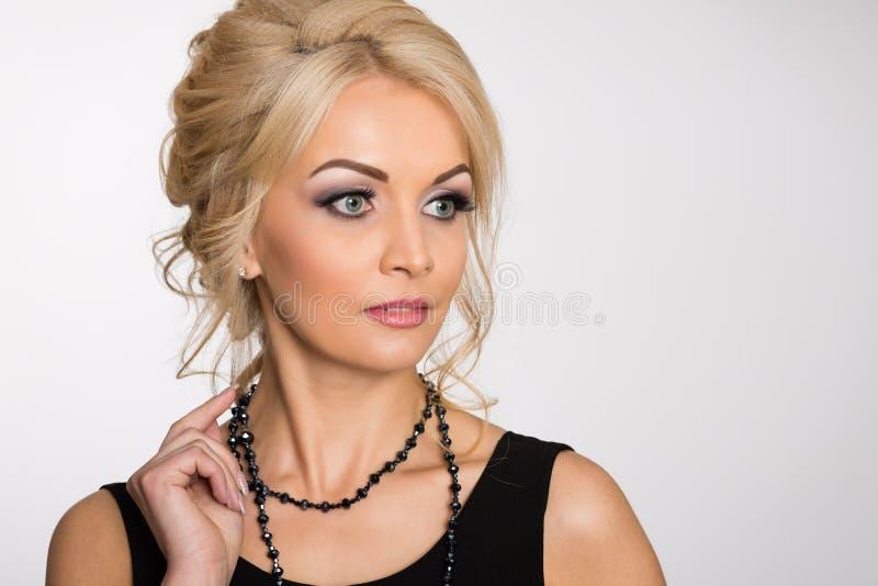 Menina bonita com cabelo louro em um cinza imagem de stock royalty free