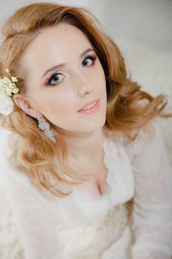 A menina bonita com cabelo louro em uma sala brilhante está encontrando-se no assoalho Noiva que encontra-se olhando a câmera e o imagem de stock royalty free