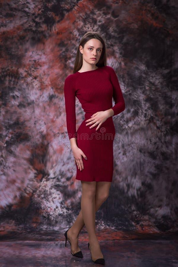 A menina bonita com cabelo marrom longo no vestido vermelho que levanta sobre o mármore coloriu o fundo Foto da forma fotografia de stock