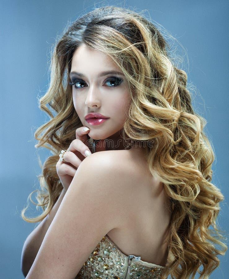 Menina bonita com cabelo ondulado longo Louro com penteado encaracolado e os bordos cor-de-rosa imagens de stock royalty free