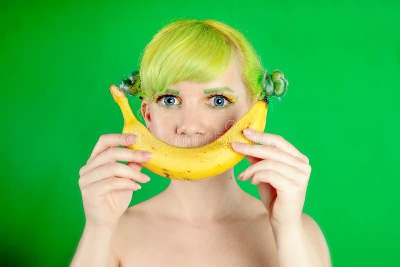 A menina bonita com cabelo verde sorri com a banana no fundo verde imagens de stock royalty free