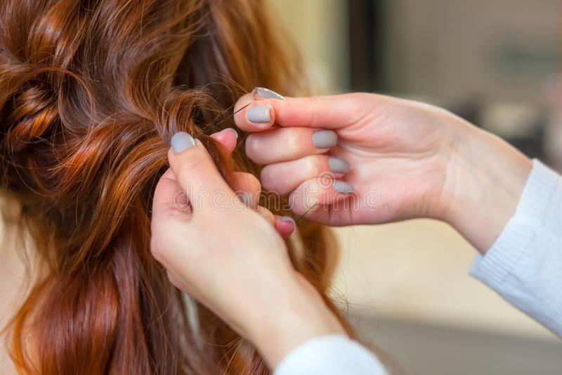 A menina bonita com cabelo vermelho, cabeleireiro tece um close-up da trança, em um salão de beleza foto de stock