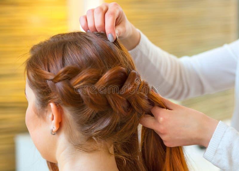 A menina bonita com cabelo vermelho longo, cabeleireiro tece uma trança, em um salão de beleza imagem de stock royalty free