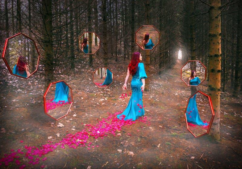 Menina bonita com cabelo vermelho no vestido azul que passa a floresta da calha com reflexão em espelhos abstratos e nas pétalas  fotos de stock royalty free