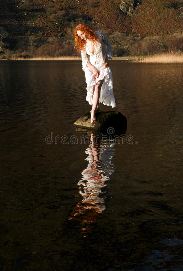 A menina bonita com cabelo vermelho refletiu nas ondinhas e ainda molha imagens de stock