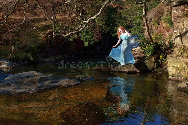A menina bonita com cabelo vermelho refletiu nas ondinhas e ainda na água de uma associação rochosa foto de stock royalty free