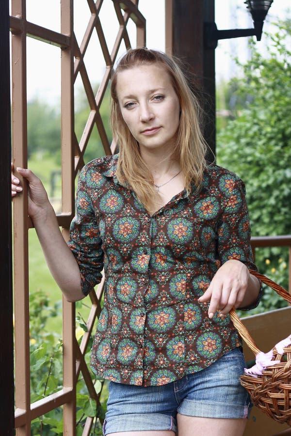 Menina bonita com a cesta no jardim imagem de stock royalty free