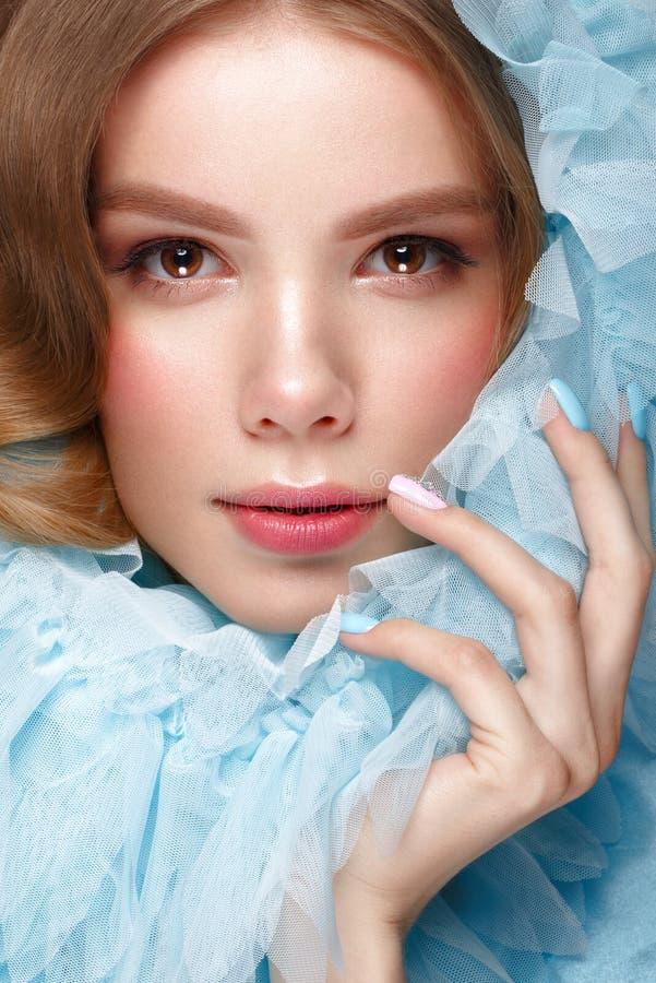 Menina bonita com composição clara e tratamento de mãos delicado na roupa azul Face da beleza Pregos do projeto imagens de stock