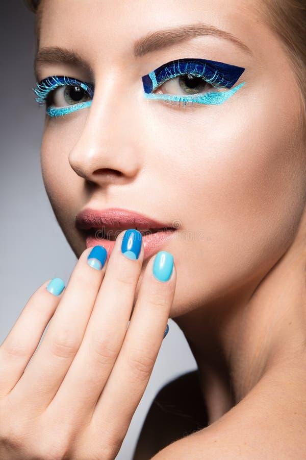 Menina bonita com composição criativa brilhante da forma e verniz para as unhas azul Projeto da beleza da arte fotos de stock royalty free