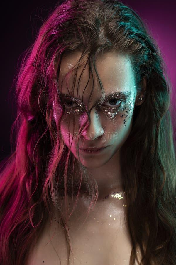 Menina bonita com a composição criativa feita do brilho com os rasgos em sua cara iluminada com luz cor-de-rosa e azul foto de stock royalty free