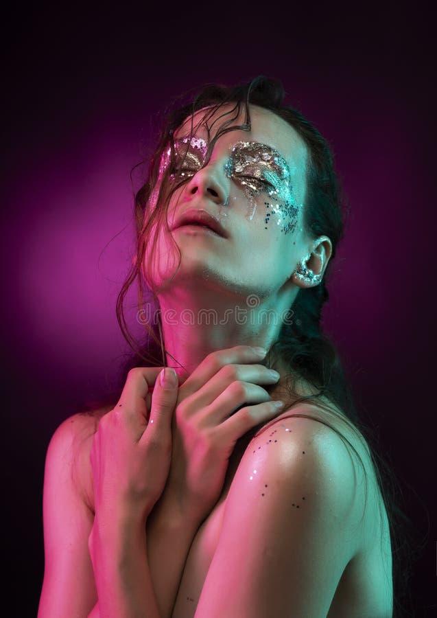 Menina bonita com a composição criativa feita do brilho com os rasgos em sua cara iluminada com luz cor-de-rosa e azul imagens de stock