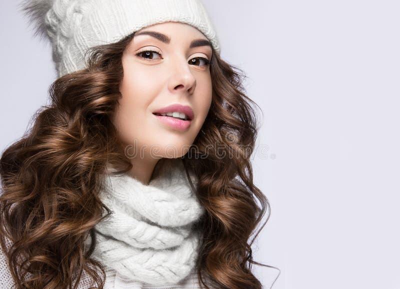 Menina bonita com composição delicada, ondas e sorriso no chapéu branco da malha Imagem morna do inverno Face da beleza foto de stock royalty free