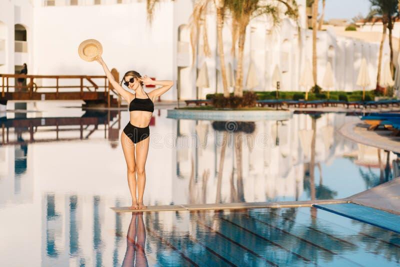 Menina bonita com corpo magro, roupa de banho preto vestindo modelo que levanta no meio da associação no hotel de luxo, recurso imagens de stock