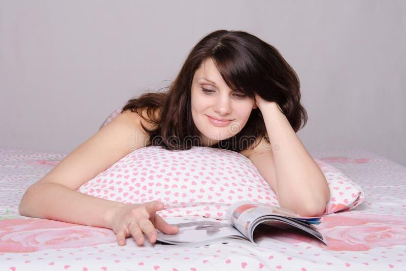 A menina bonita com entusiasmo lê o compartimento na cama foto de stock royalty free