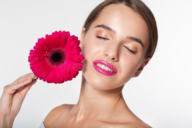 Menina bonita com a flor do gerbera perto da cara foto de stock royalty free