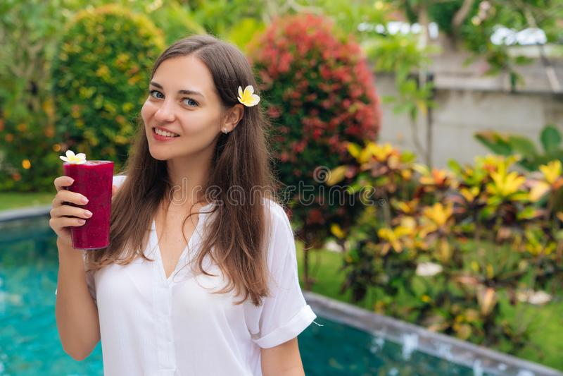 Menina bonita com a flor em seus cabelo e vidros de suportes do batido de fruta do dragão no jardim tropical imagens de stock