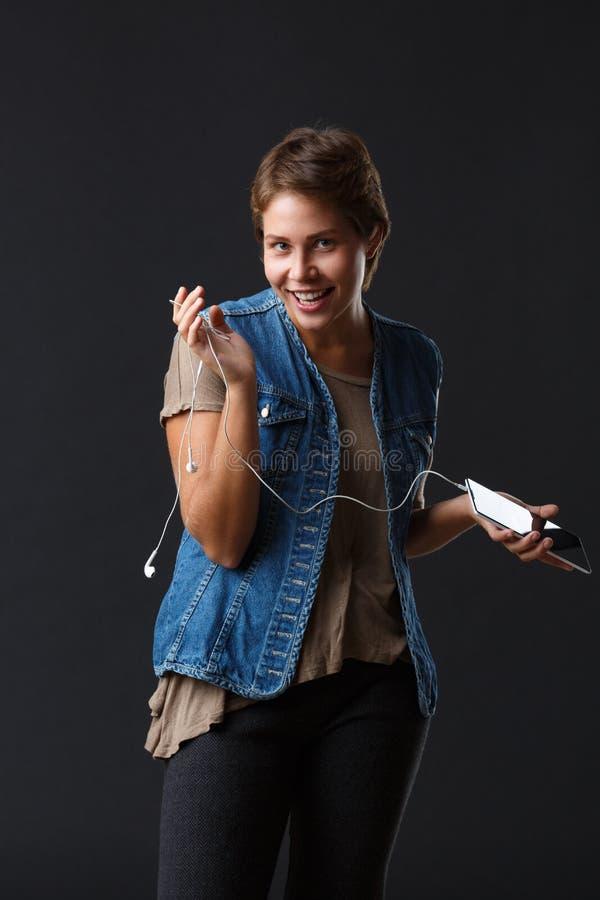 Menina bonita com fones de ouvido e seu telefone em um fundo preto fotografia de stock