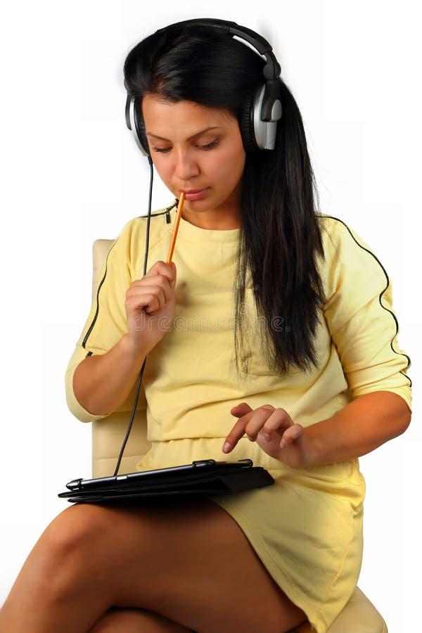 Menina bonita com fones de ouvido e uma tabuleta do computador fotos de stock royalty free