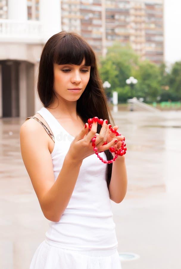 Menina bonita com grânulos vermelhos imagem de stock royalty free
