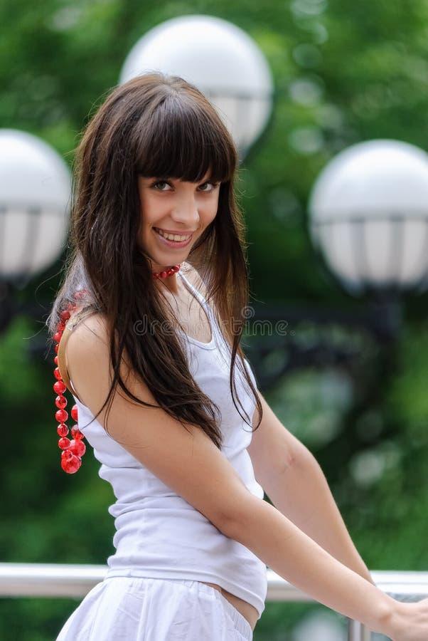 Menina bonita com grânulos vermelhos fotografia de stock royalty free
