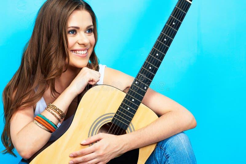 Menina bonita com a guitarra contra o fundo azul fotografia de stock