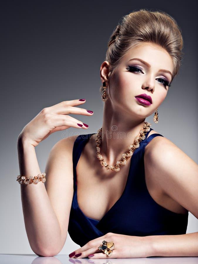 Menina bonita com joia bonita do penteado e do ouro, m brilhante fotografia de stock royalty free