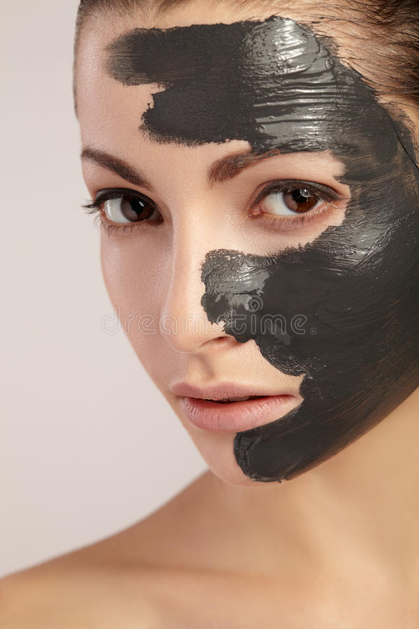 Menina bonita com máscara da argila em sua cara foto de stock royalty free