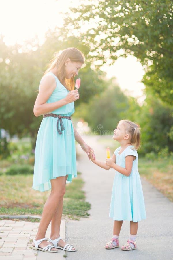 Menina bonita com a mãe que come fora o gelado no parque imagens de stock