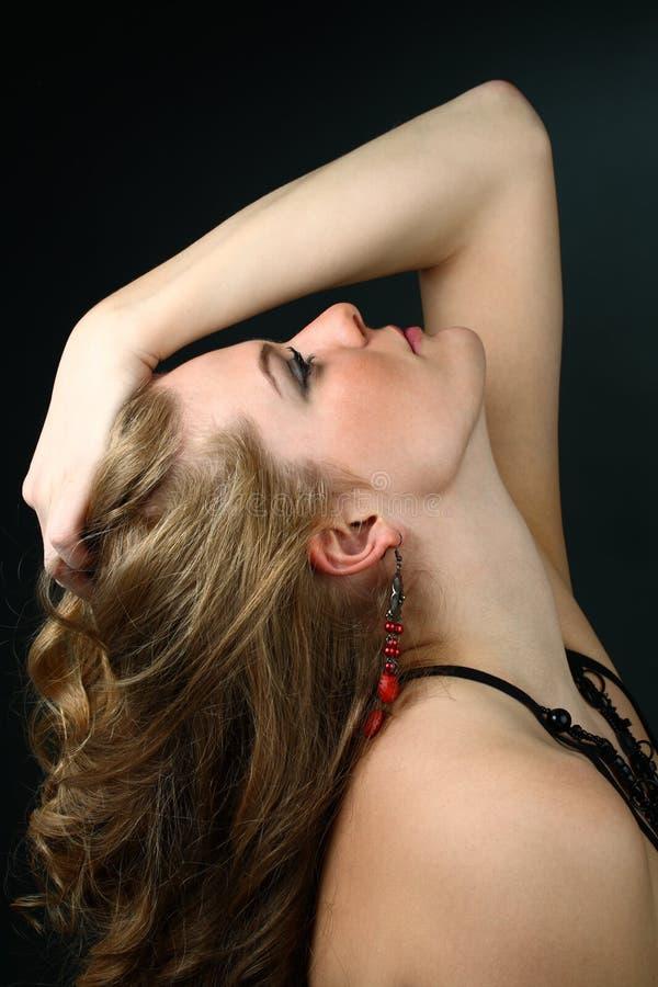 Menina bonita com mão em seu cabelo que olha acima imagens de stock