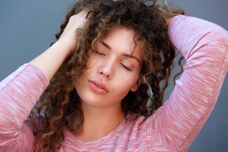 Menina bonita com mãos no cabelo e nos olhos fechados imagens de stock