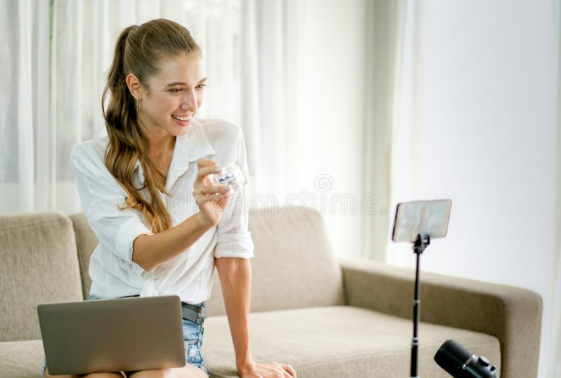 Menina bonita com mostra branca da camisa e revisão viva o produto cosmético na parte dianteira a câmera do telefone celular com  foto de stock royalty free