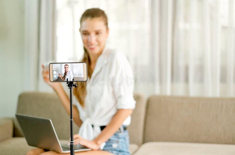 Menina bonita com mostra branca da camisa e revisão viva o produto cosmético na parte dianteira a câmera do telefone celular com  imagem de stock royalty free