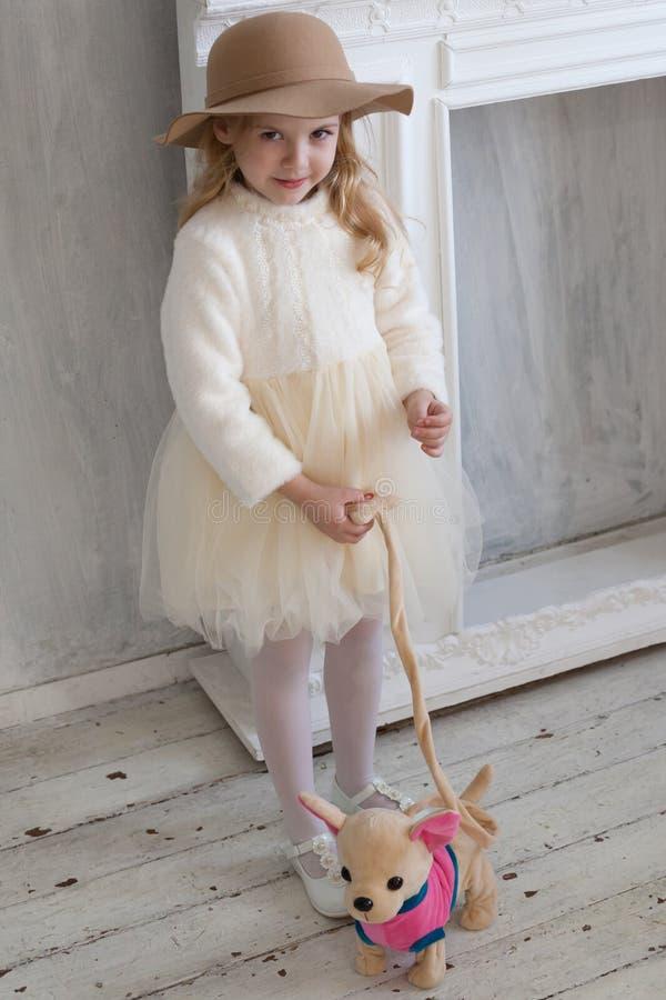 Menina bonita com o cão de cachorrinho macio do brinquedo foto de stock royalty free
