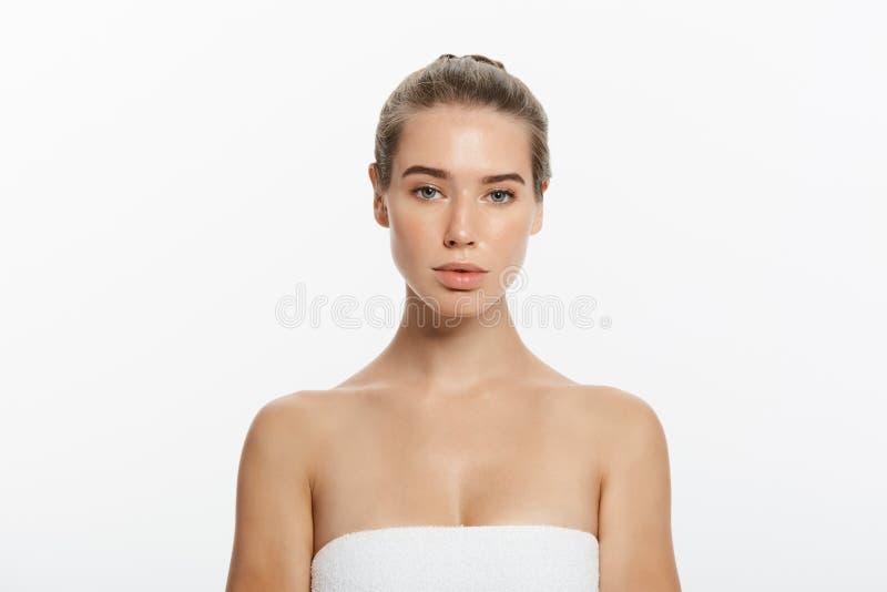 Menina bonita com o cabelo do marrom escuro fixado atrás, os olhos grandes, as sobrancelhas escuras e os ombros despidos olhando  fotografia de stock