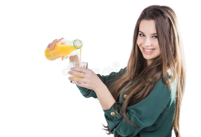 Menina bonita com o cabelo escuro que derrama de uma garrafa em um vidro do suco de laranja em um fundo branco fotografia de stock royalty free
