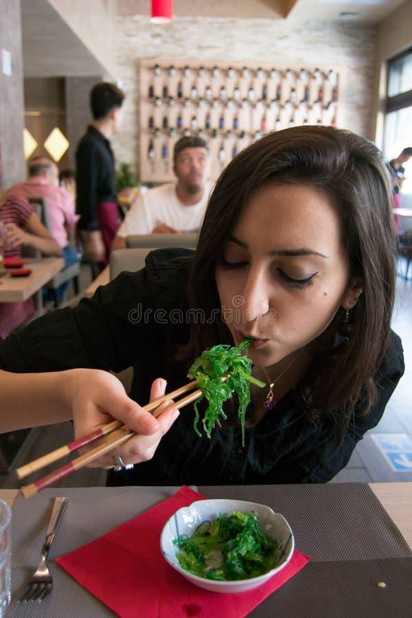 A menina bonita com o cabelo escuro, vestido no preto está comendo a salada fresca verde das algas com hashis em um restaurante fotografia de stock