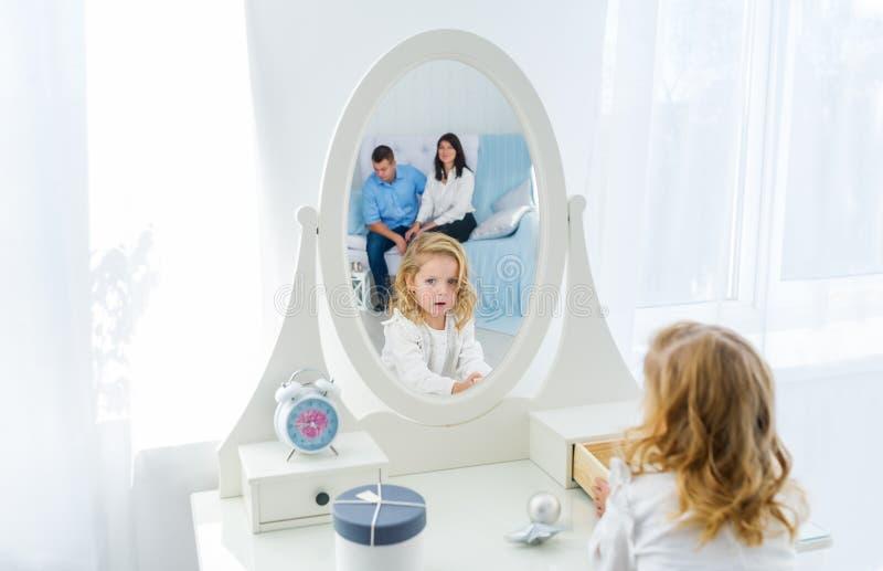 Menina bonita com o cabelo longo louro, olhando si mesma no espelho dentro A mãe e o pai estão na reflexão foto de stock royalty free