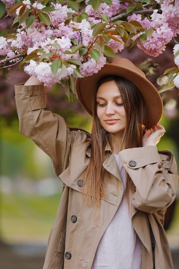 Menina bonita com o cabelo longo que guarda o ramo de sakura entre as flores de cerejeira cor-de-rosa na mola Acessórios e cl à m imagem de stock royalty free