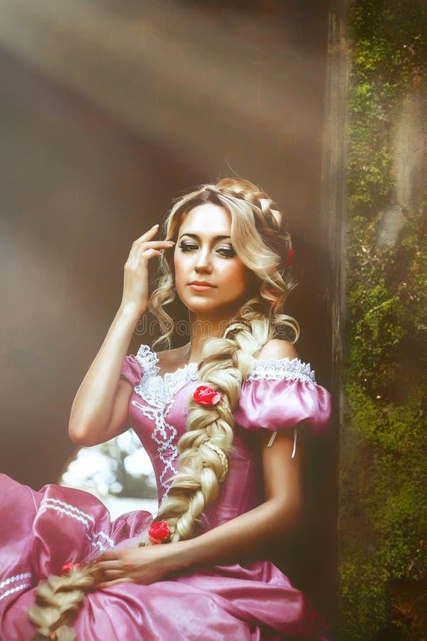 Menina bonita com o cabelo longo trançado em uma trança, no espartilho e no vestido cor-de-rosa magnífico imagem de stock royalty free