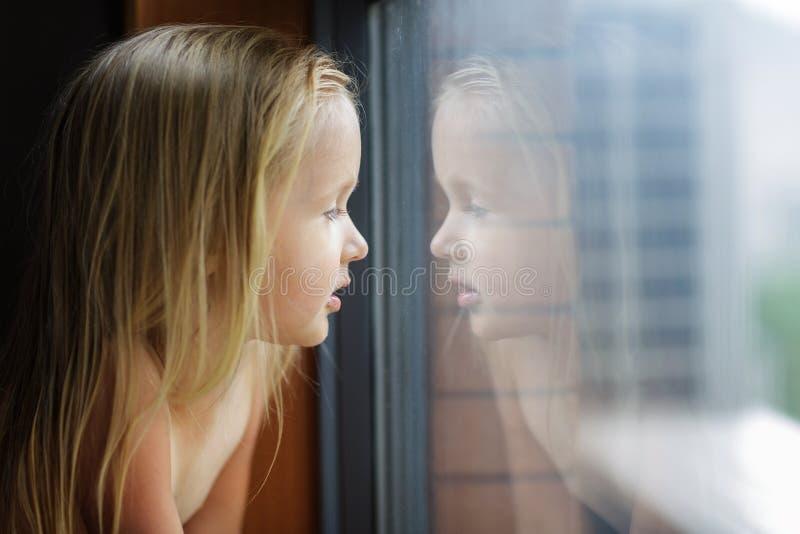 Menina bonita com o cabelo louro que olha em uma janela em casa imagem de stock royalty free
